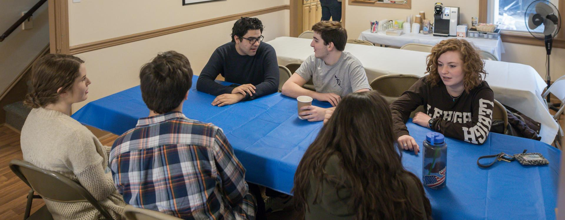 group of students talking at a table